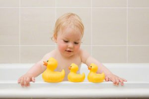 A baby boy looking at a row of rubber ducks